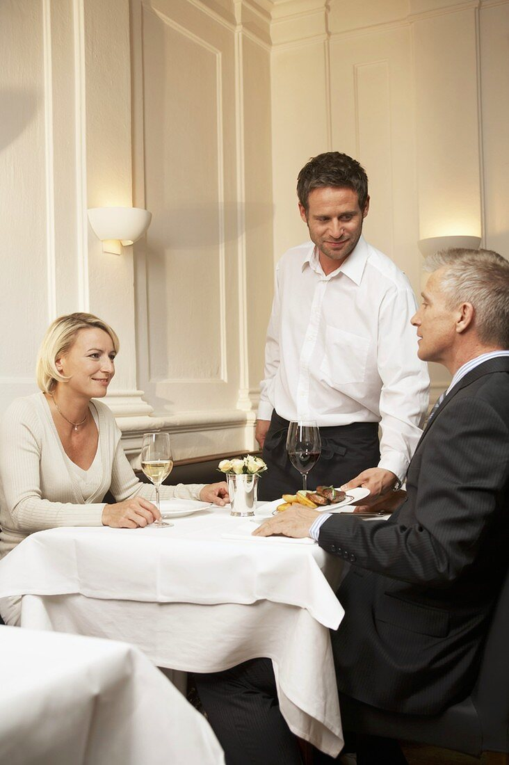 Waiter serving a married couple in a restaurant