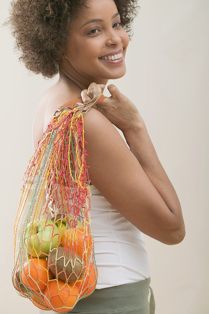 Young woman with a string bag full of fruit