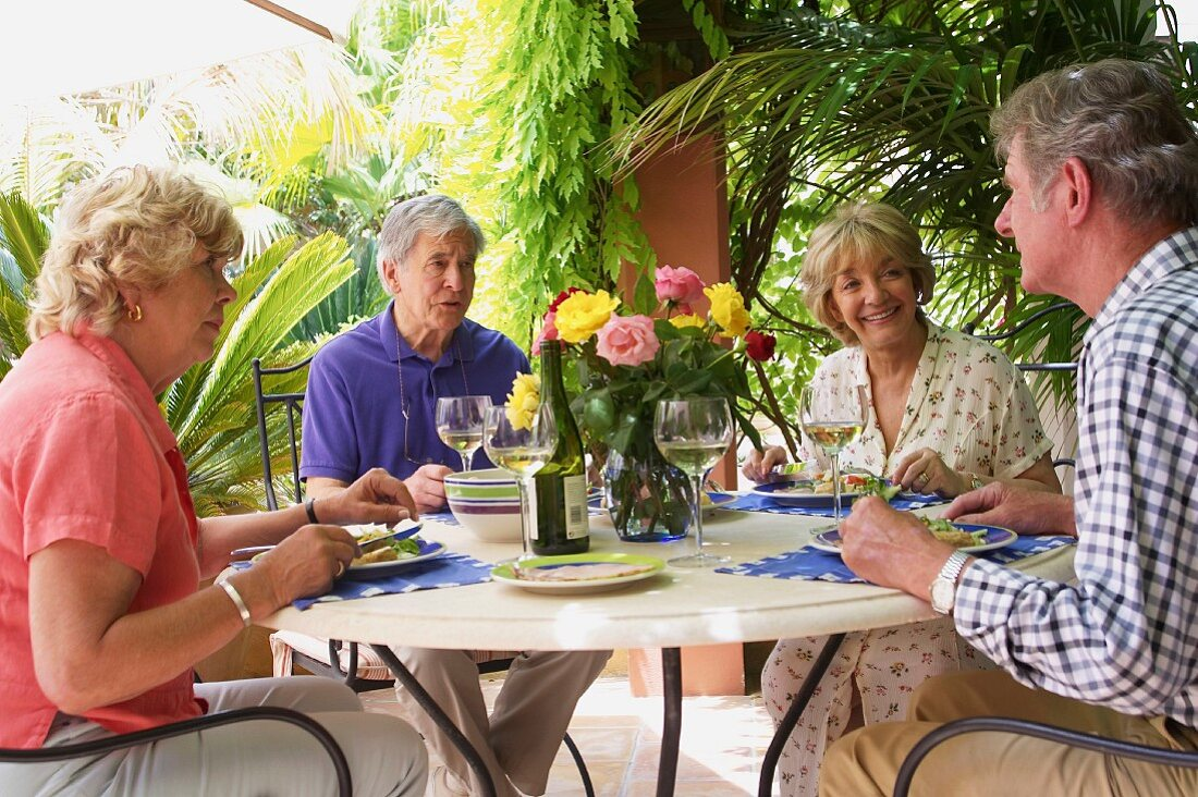 Older married couples eating on a terrace