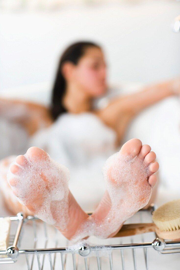 Feet of a woman lying in a bathtub