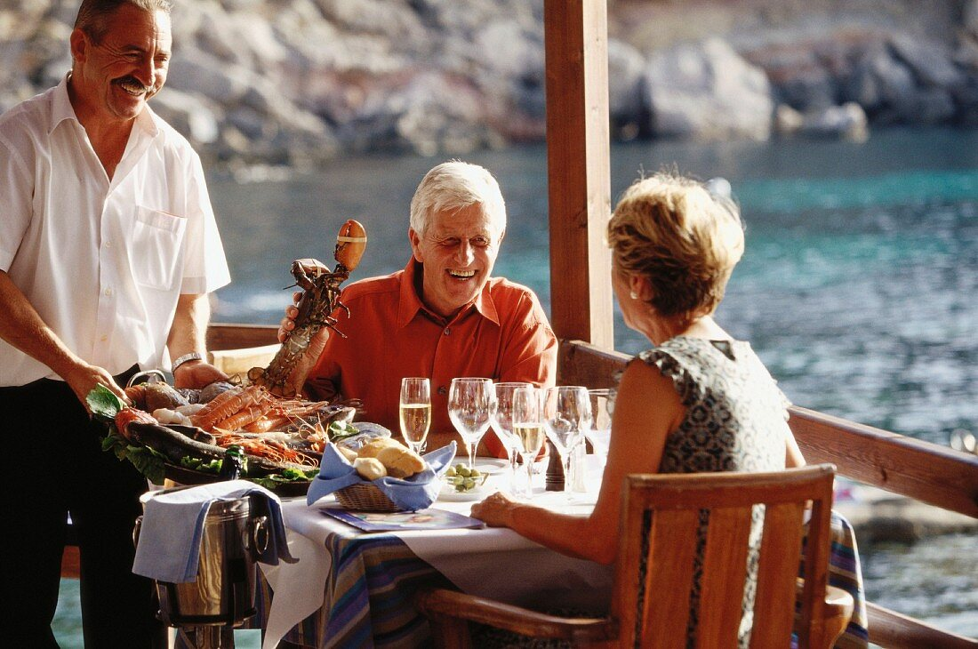 Older married couple eating lobster on holiday