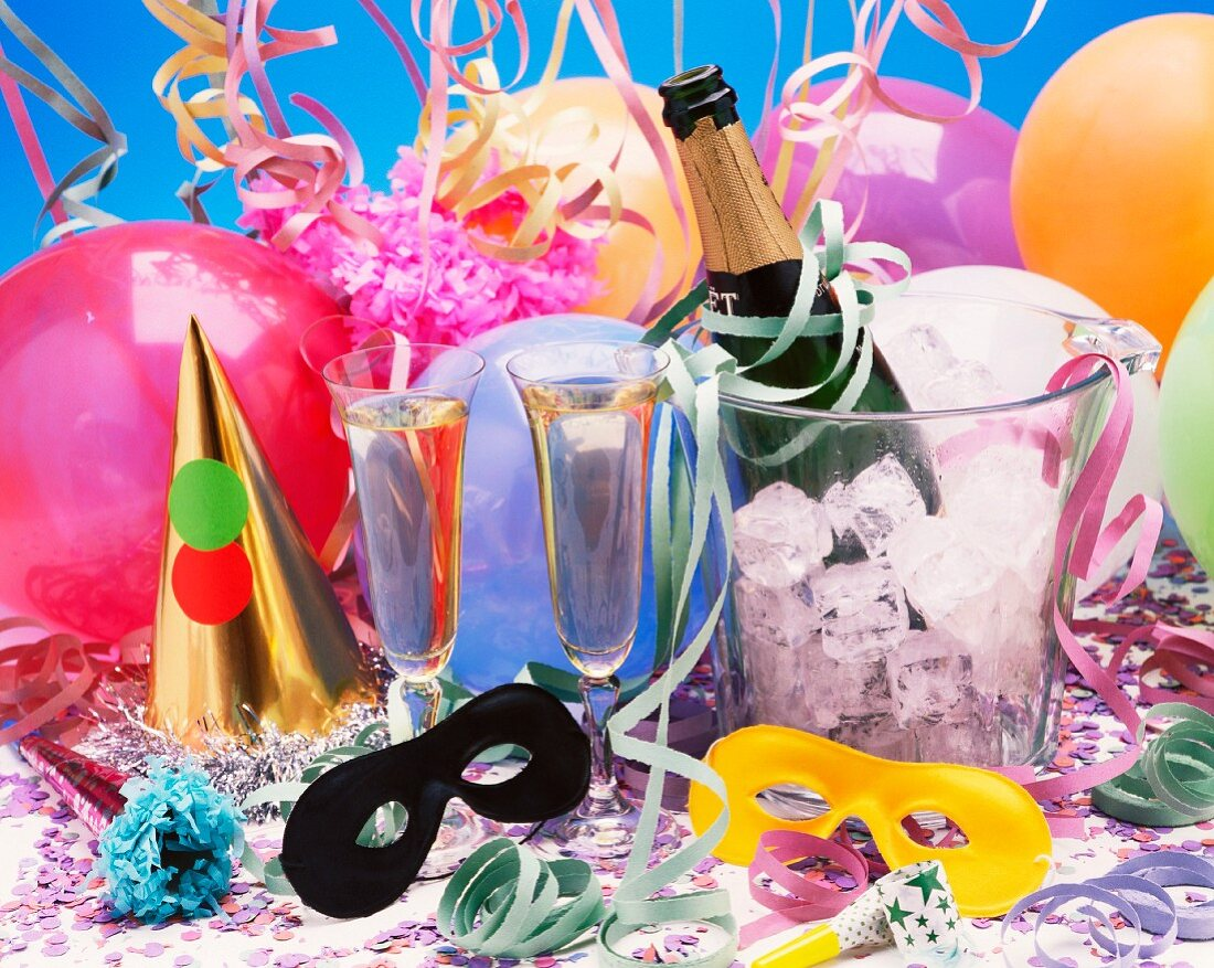 A party table with two champagne flutes, a champagne cooler and balloons