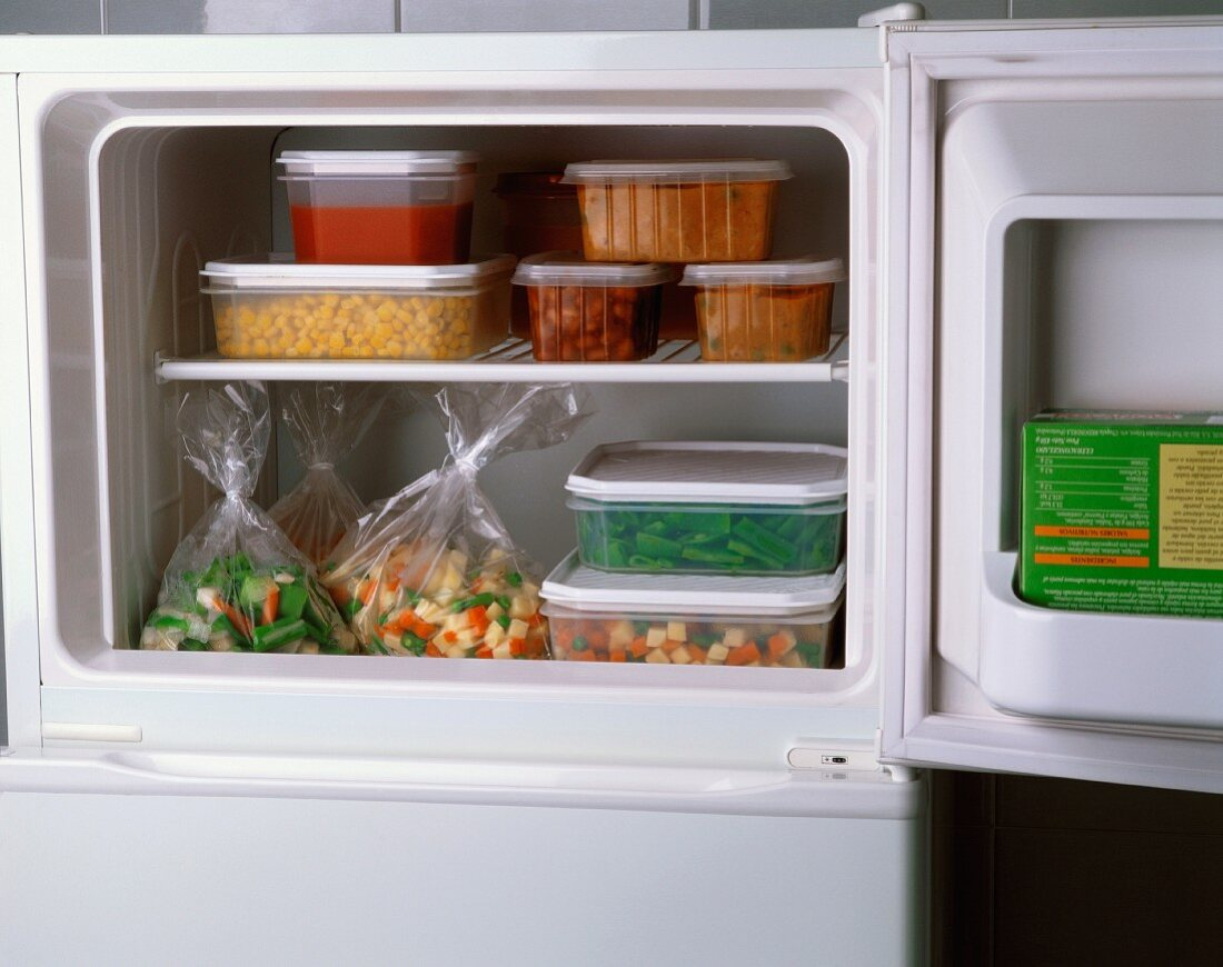 Plastic boxes of food packed into a freezer compartment