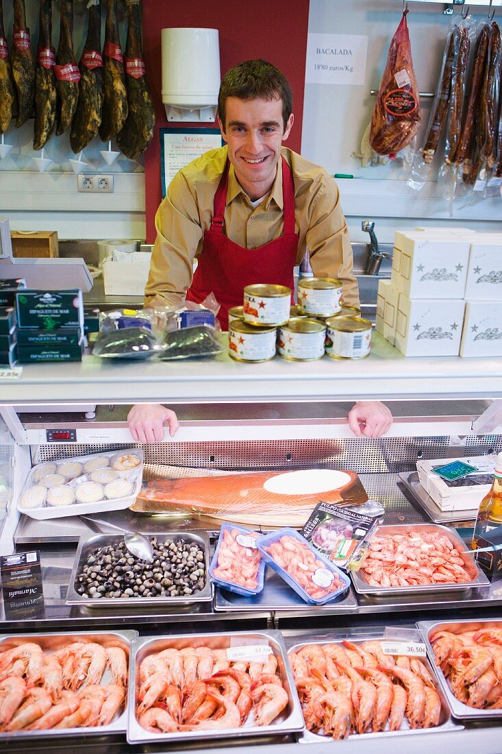 Shop assistant behind fish counter in supermarket