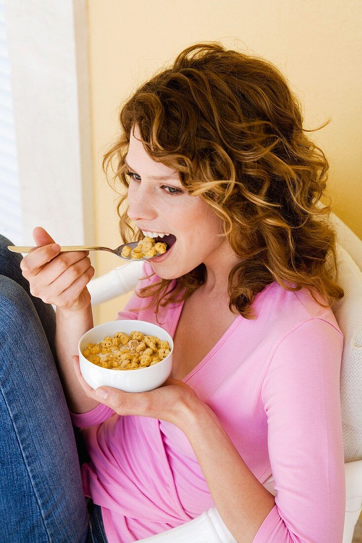Woman eating breakfast cereal from bowl