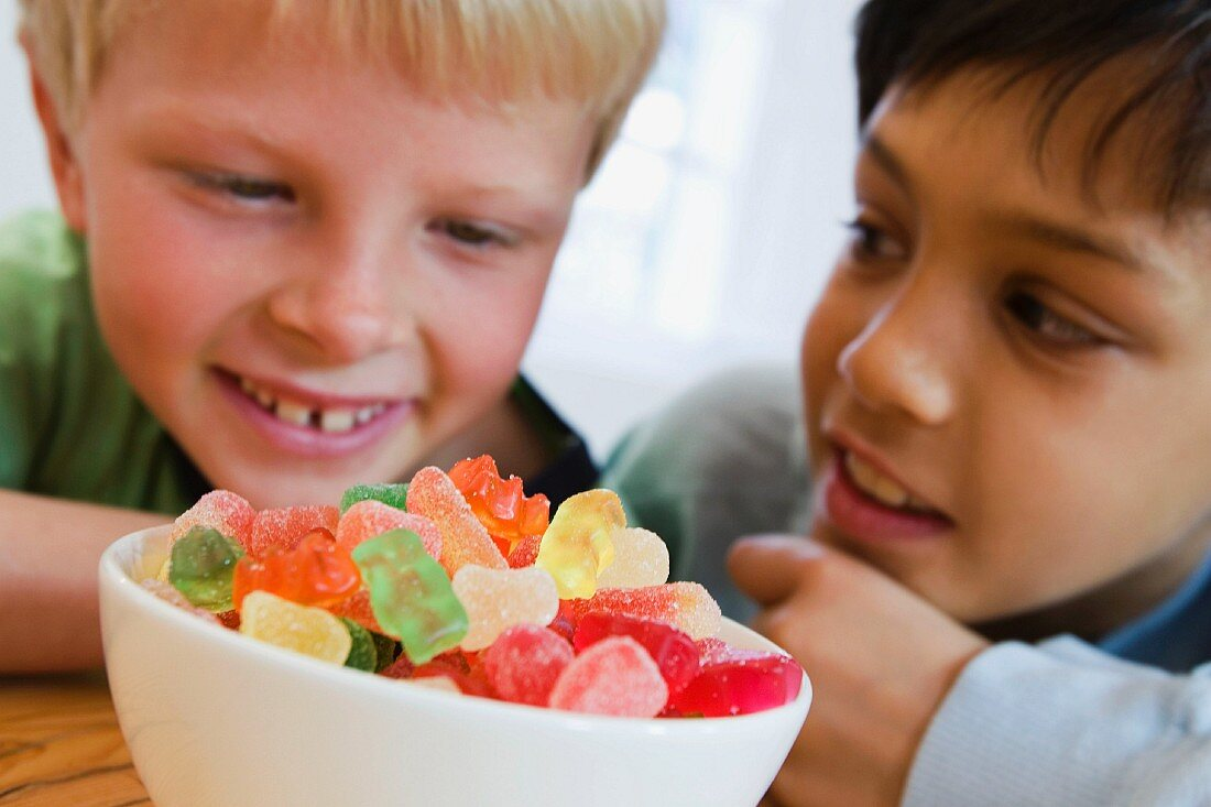 Two seated boys with bowl of fruit gums