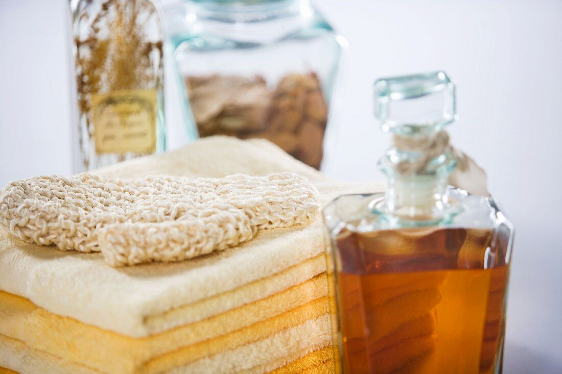Exfoliating mitt on stack of towels next to bath oil