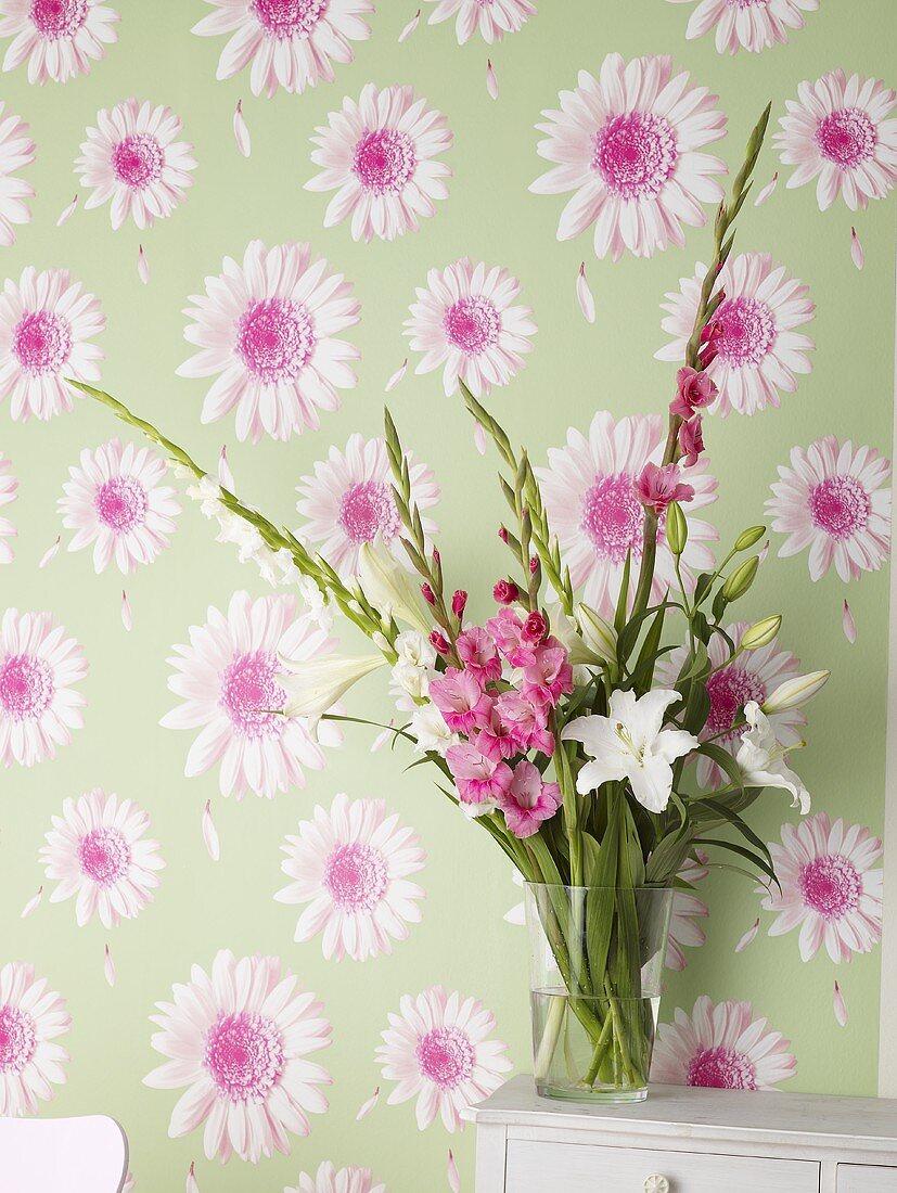 Vase of flowers against flowered wallpaper