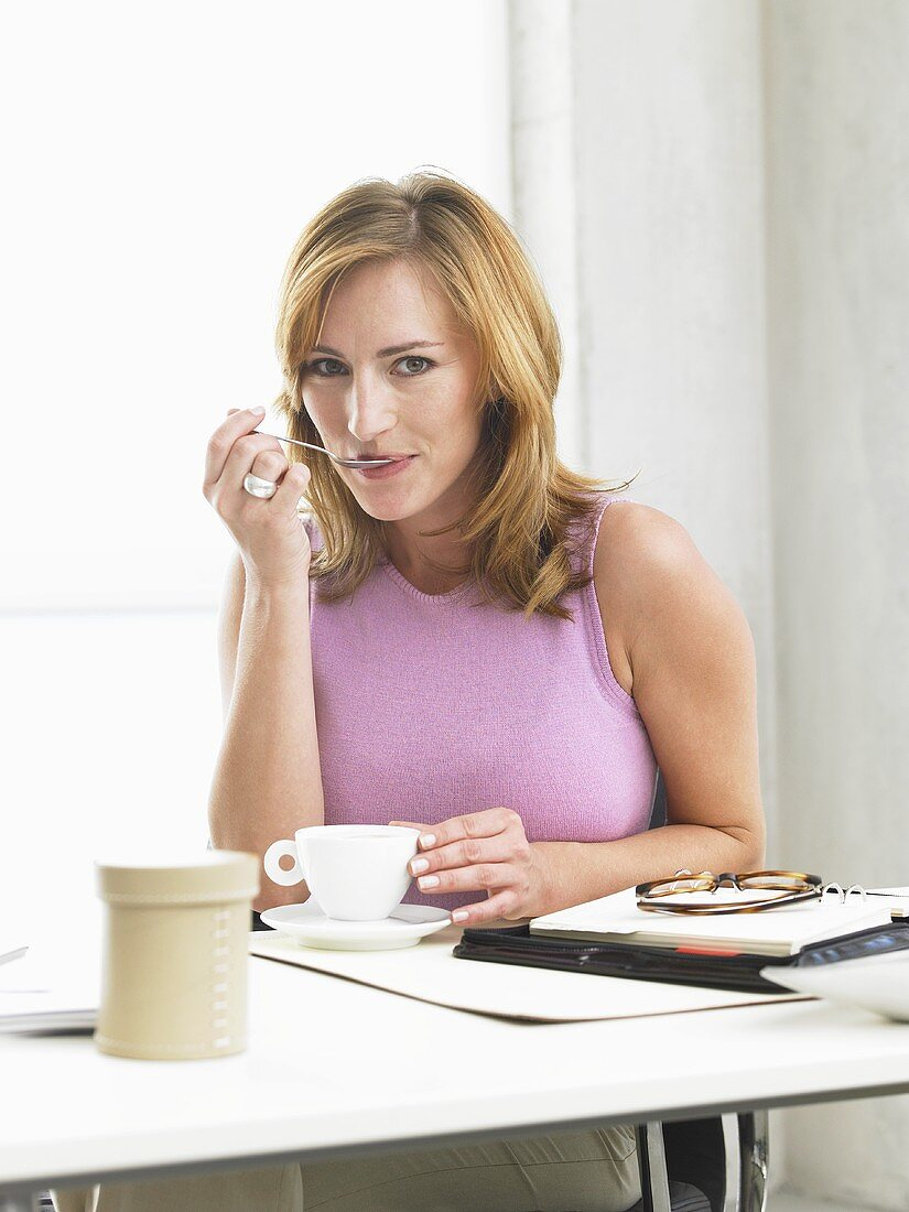 Woman drinking coffee sitting at her desk