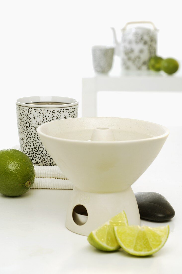 Aroma lamp with limes, tea things