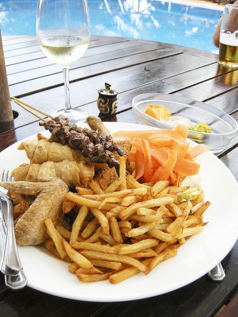 Plate of barbecued food and chips on table by swimming pool