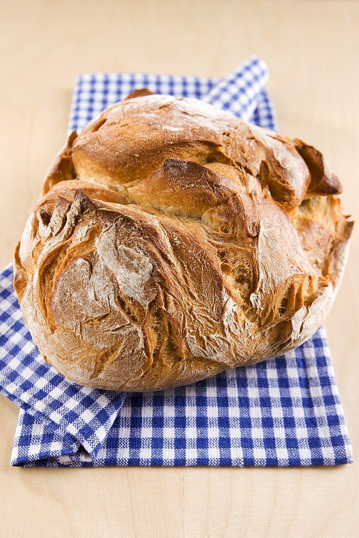 Rustic loaf of bread on checked cloth