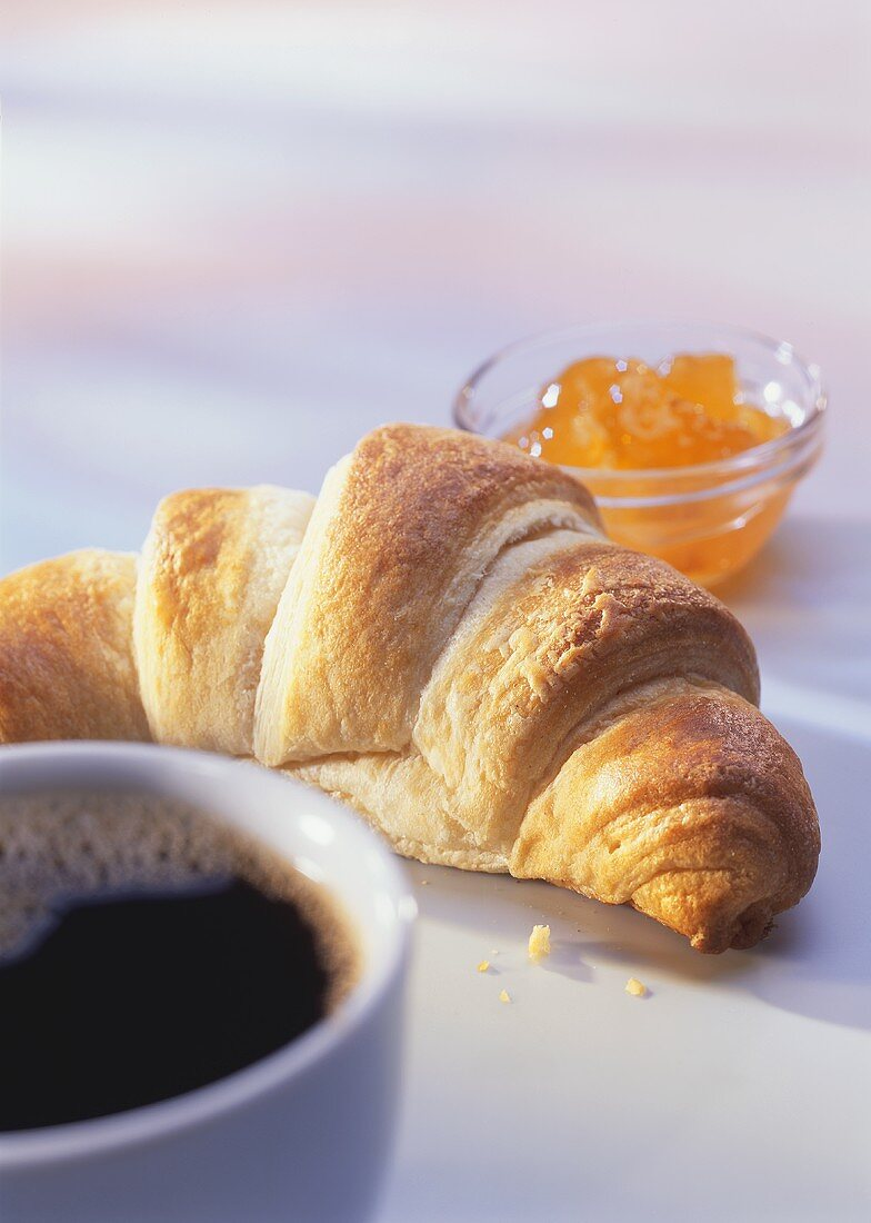A croissant, marmalade and a cup of coffee