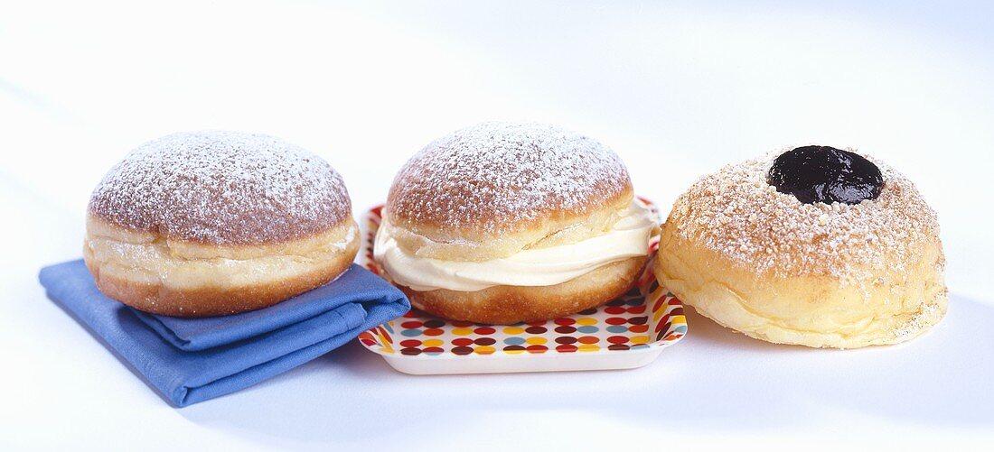 Three doughnuts with plum jelly, vanilla cream and jam
