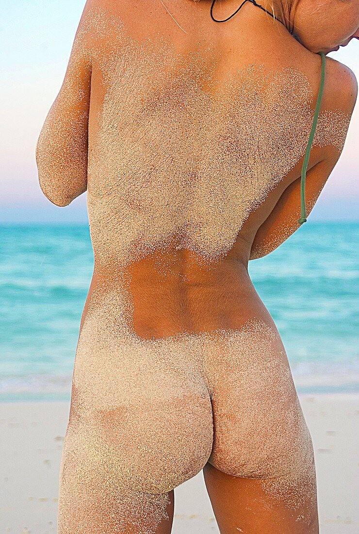 Back view of a naked woman on a sandy beach