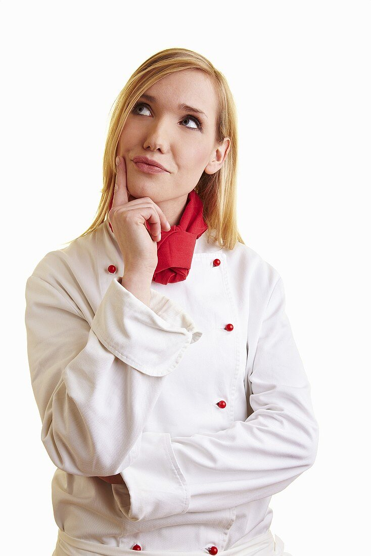 Thoughtful blond female chef in work clothes