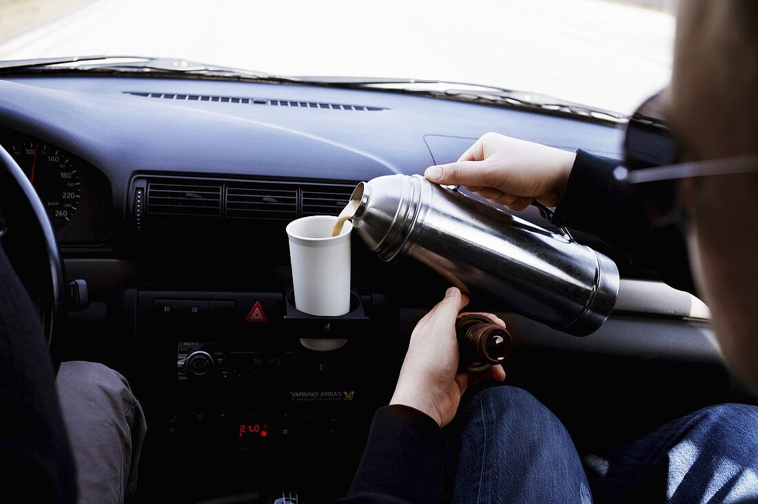 Pouring coffee out of thermos in a car into a cup