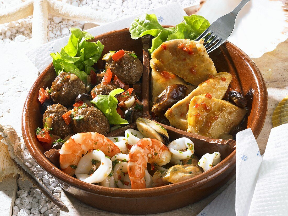 Assorted tapas (Moorish chicken, seafood salad, meatballs)
