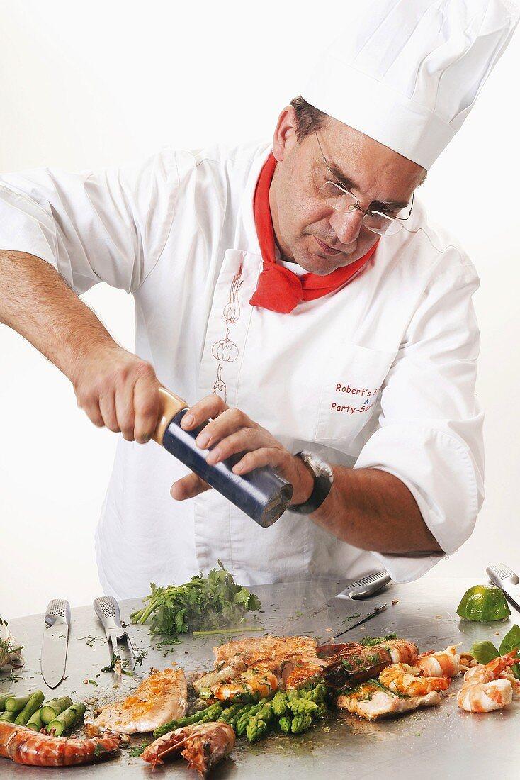 Chef seasoning grilled fish and prawns