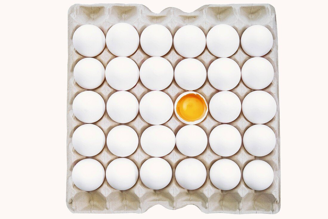White eggs in egg tray, one cracked open (overhead view)
