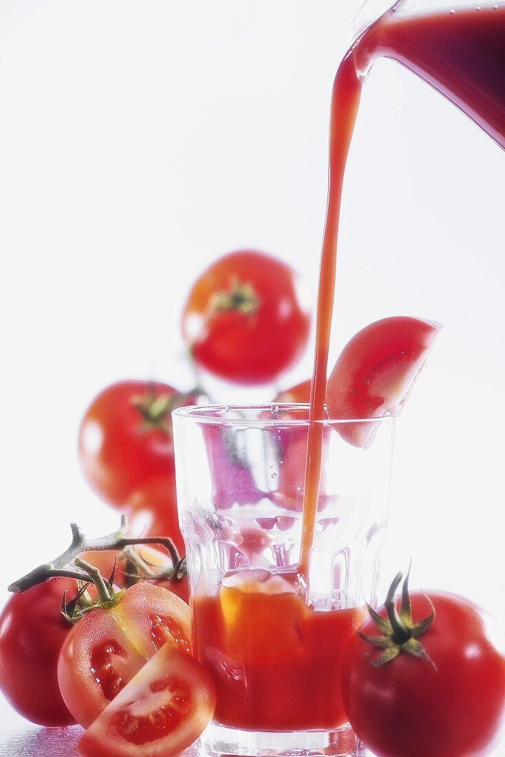 Pouring tomato juice into glass