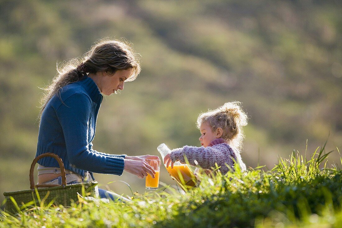 Mother and daughter in meadow with fruit juice