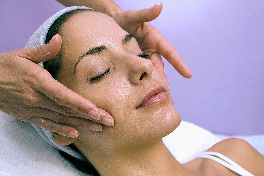 Junge Frau bei kosmetischer Behandlung (Gesichtsmassage)