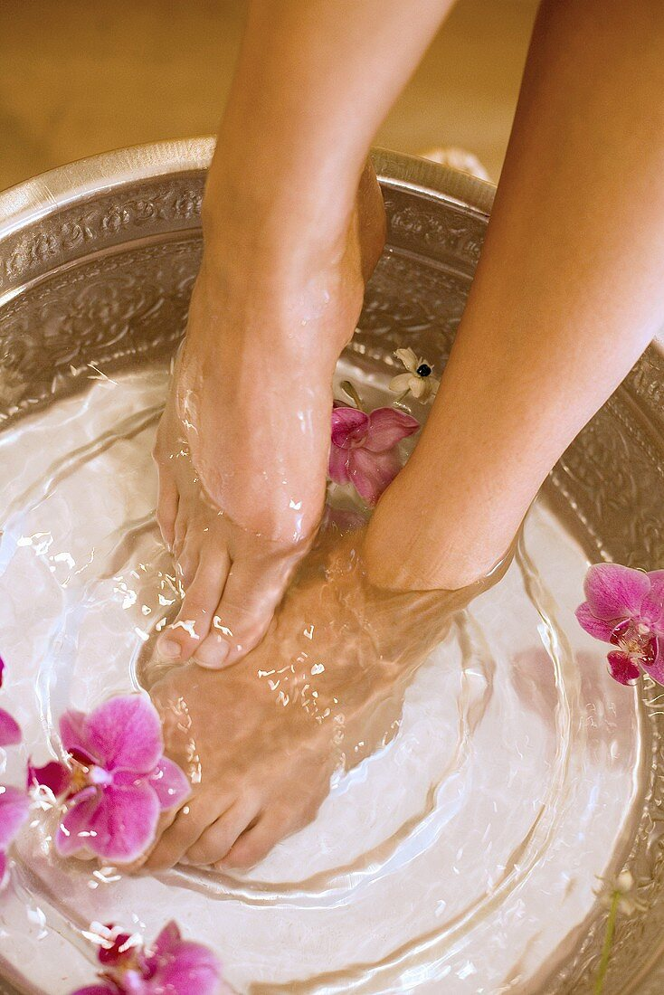 Woman taking footbath, with flowers