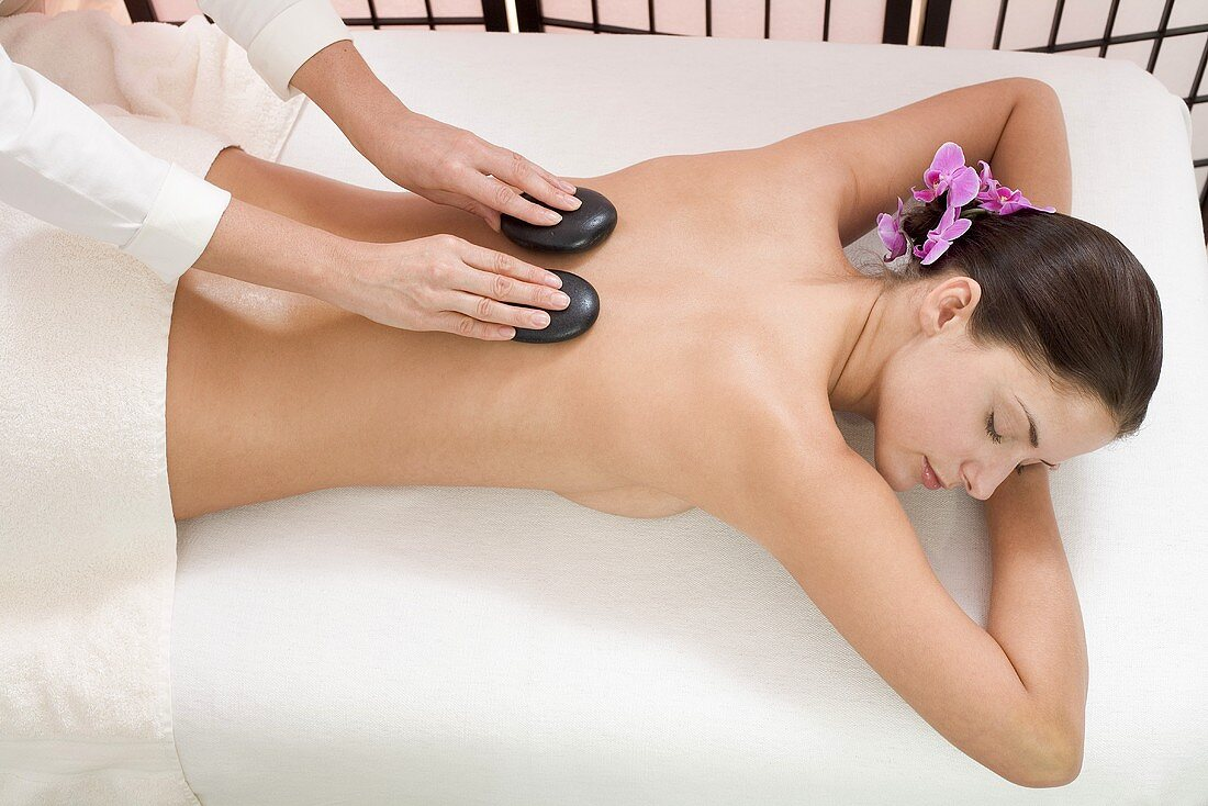 Young woman receiving hot stone massage, elevated view