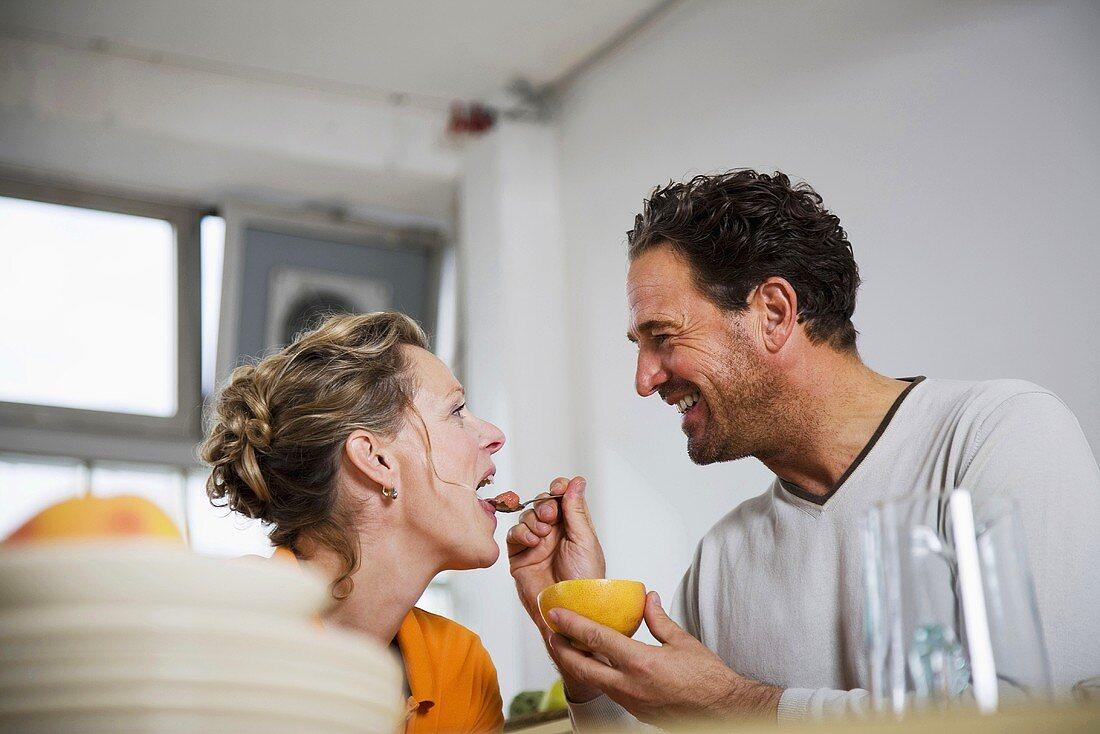 Man feeding grapefruit to woman