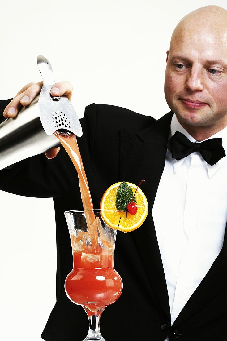 Bartender pouring cocktail into glass, portrait