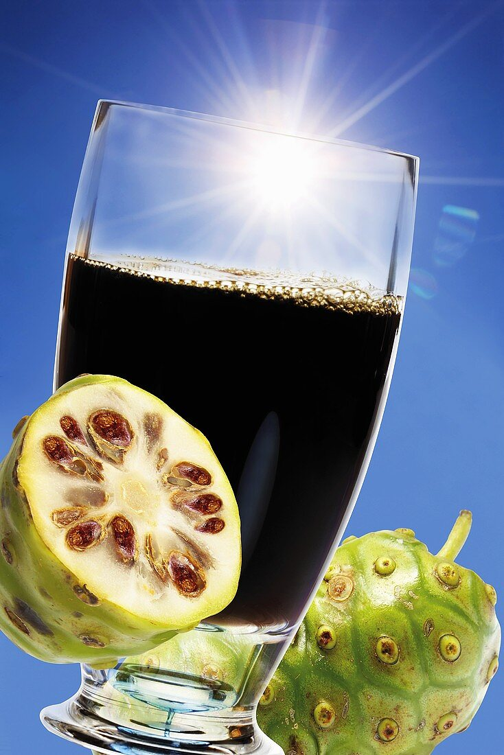 Glass of noni juice, fresh fruits