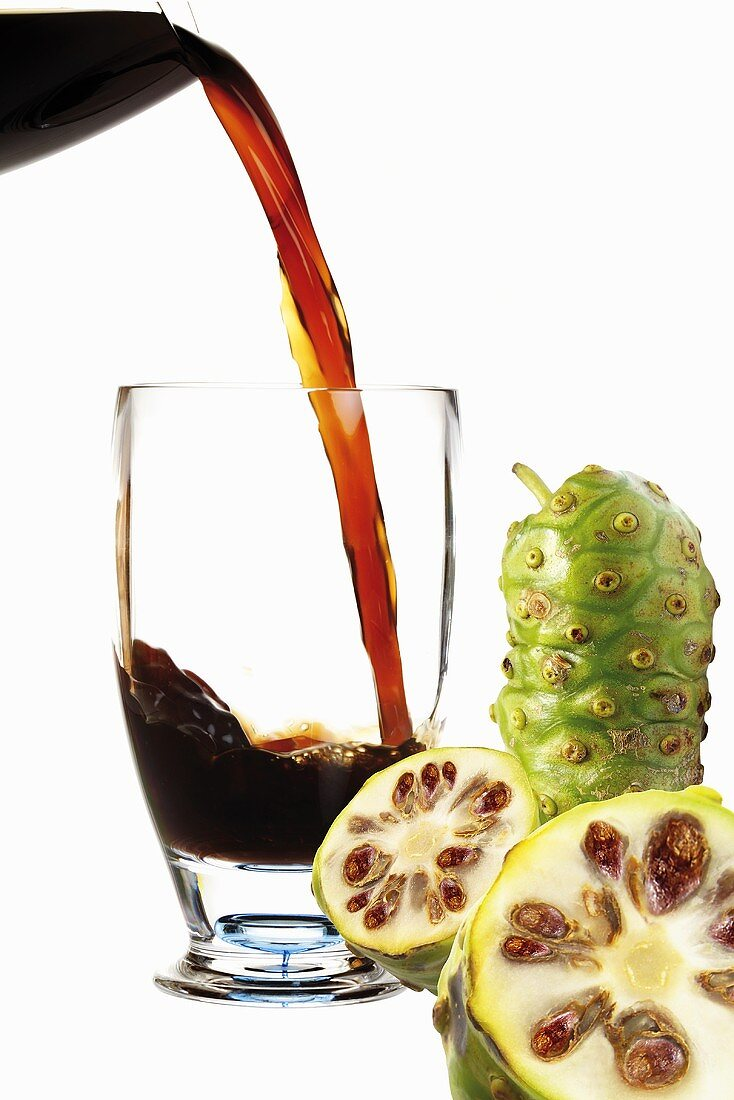 Pouring Noni juice into glass, fresh fruits aside