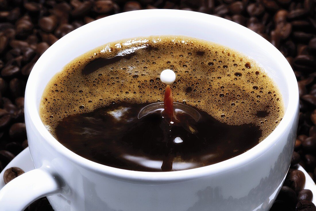Cup of coffee with drop of milk