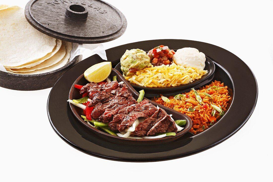 Beef fajita with accompaniments and tortillas
