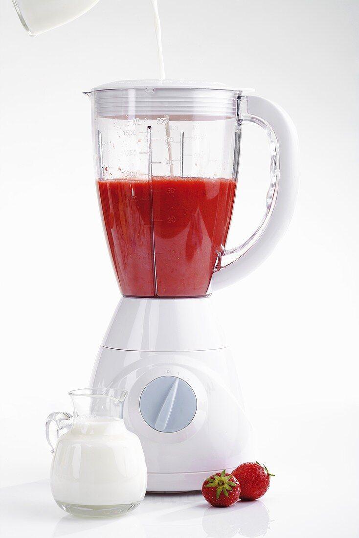 Pureed strawberries in liquidiser, adding milk
