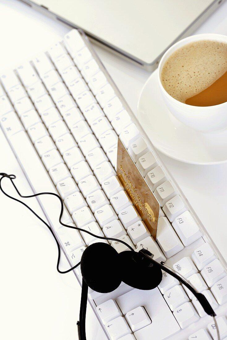 Credit card balanced on keyboard, headphones, cup of coffee