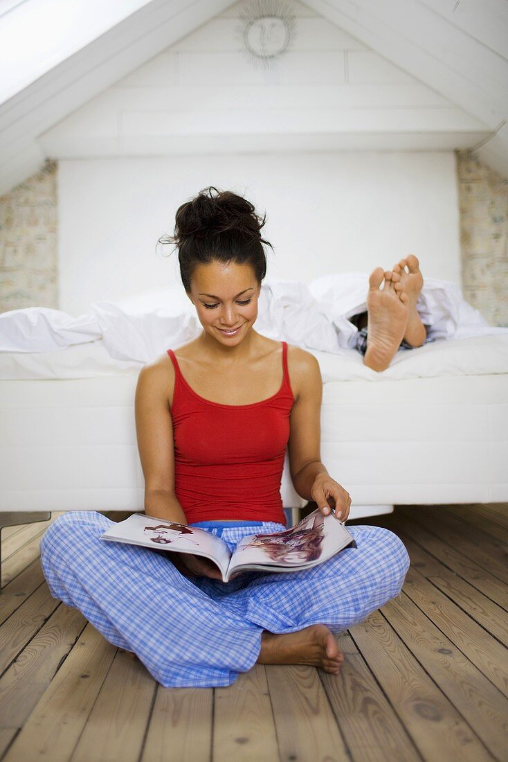 Woman leafing through magazine, man lying in bed