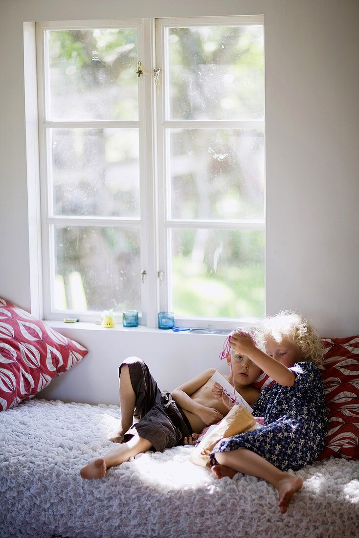 Girl and boy playing on bed