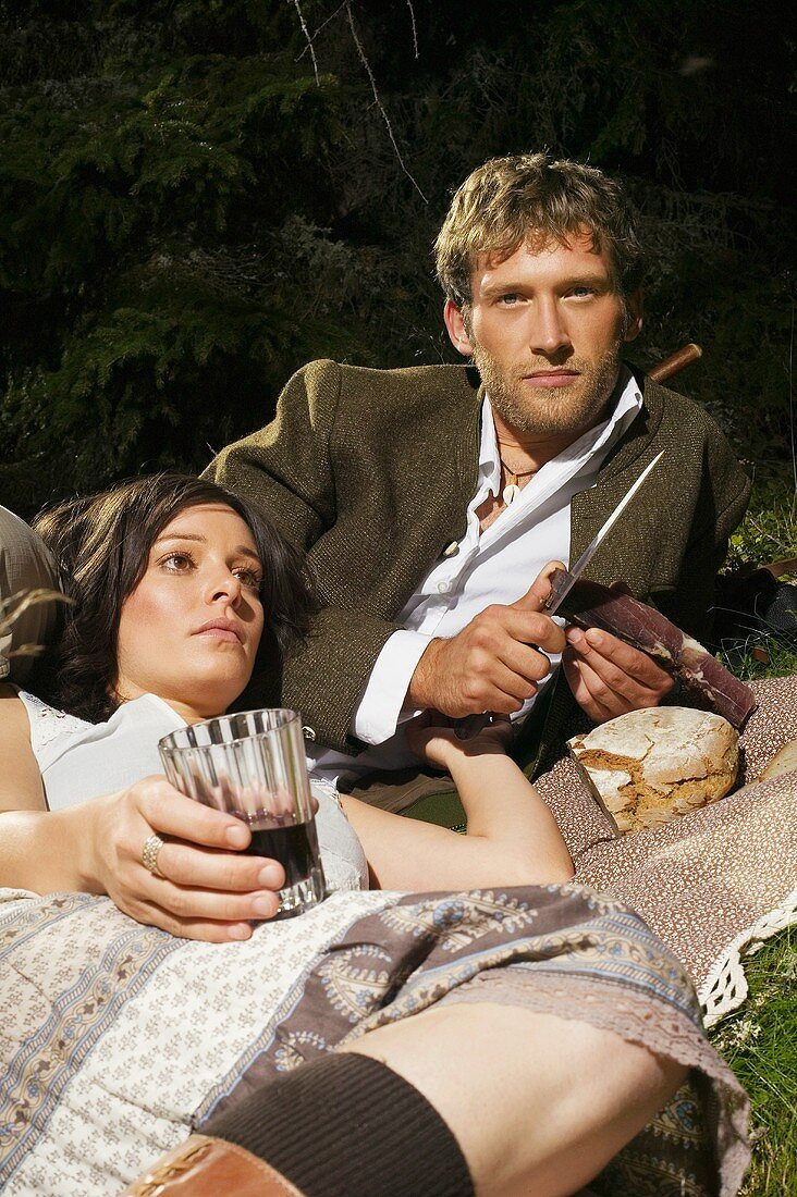 South Tyrolean couple lying in meadow, having picnic