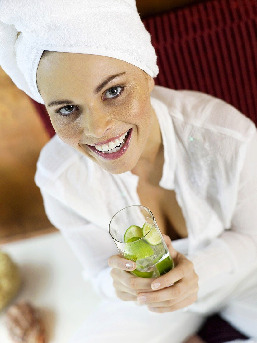 Woman sitting on cushion holding glass of lime water, close-up