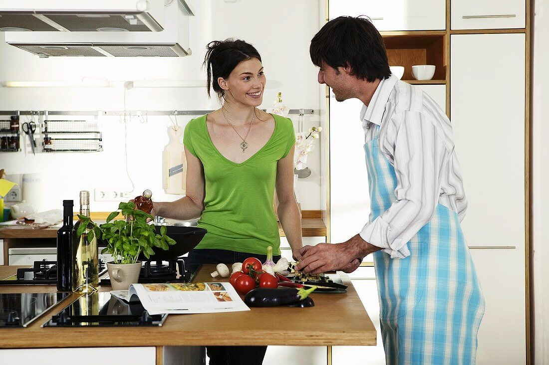 Young couple cooking food in kitchen, smiling