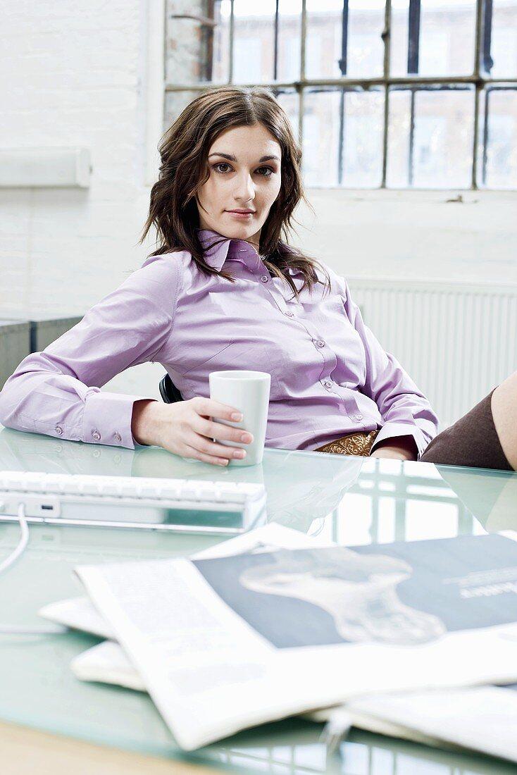 Woman having a coffee break in an office