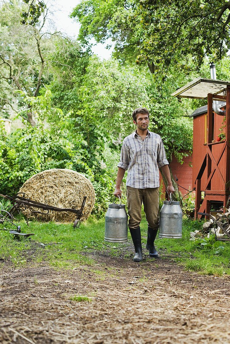 Farmer carrying milk cans