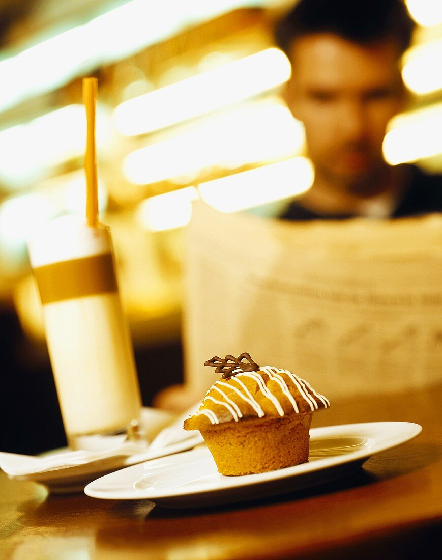 Muffin and coffee in restaurant, man reading newspaper