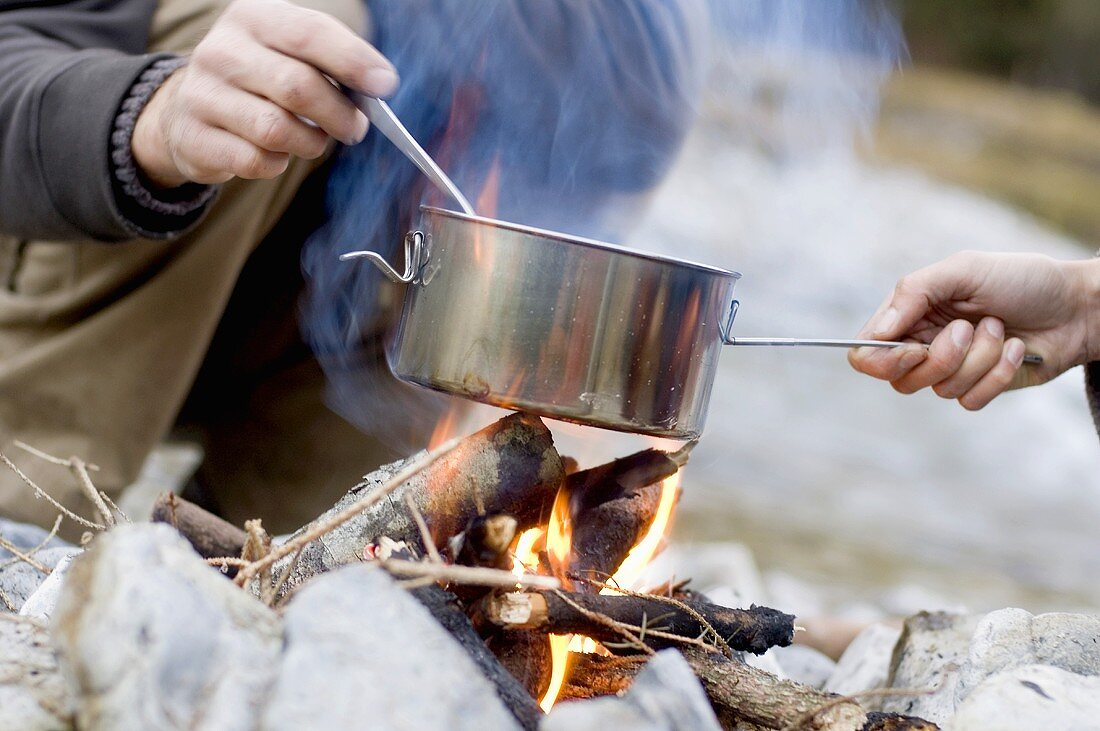 Austria, Salzburg county, Young couple cooking at campfire