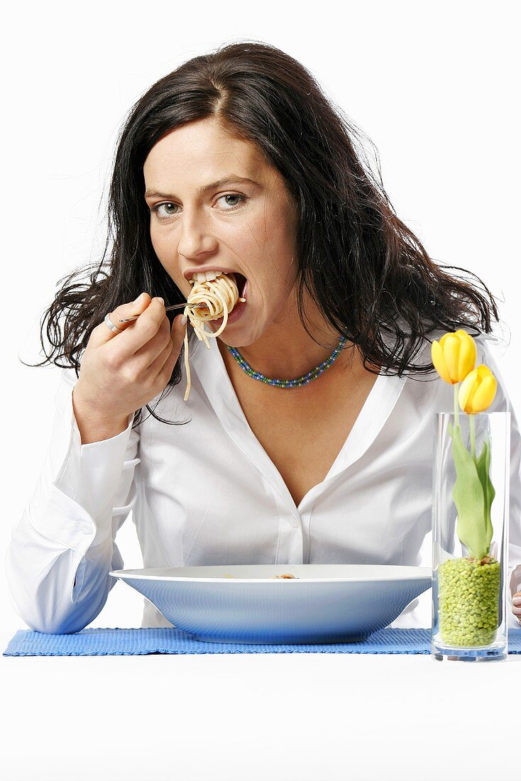 Young woman eating bowl of spaghetti with fork, portrait