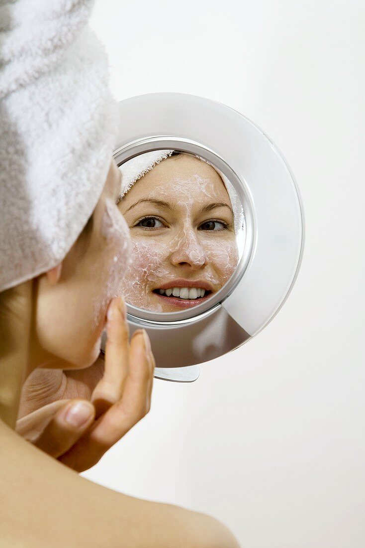Young woman applying face mask looking into mirror smiling