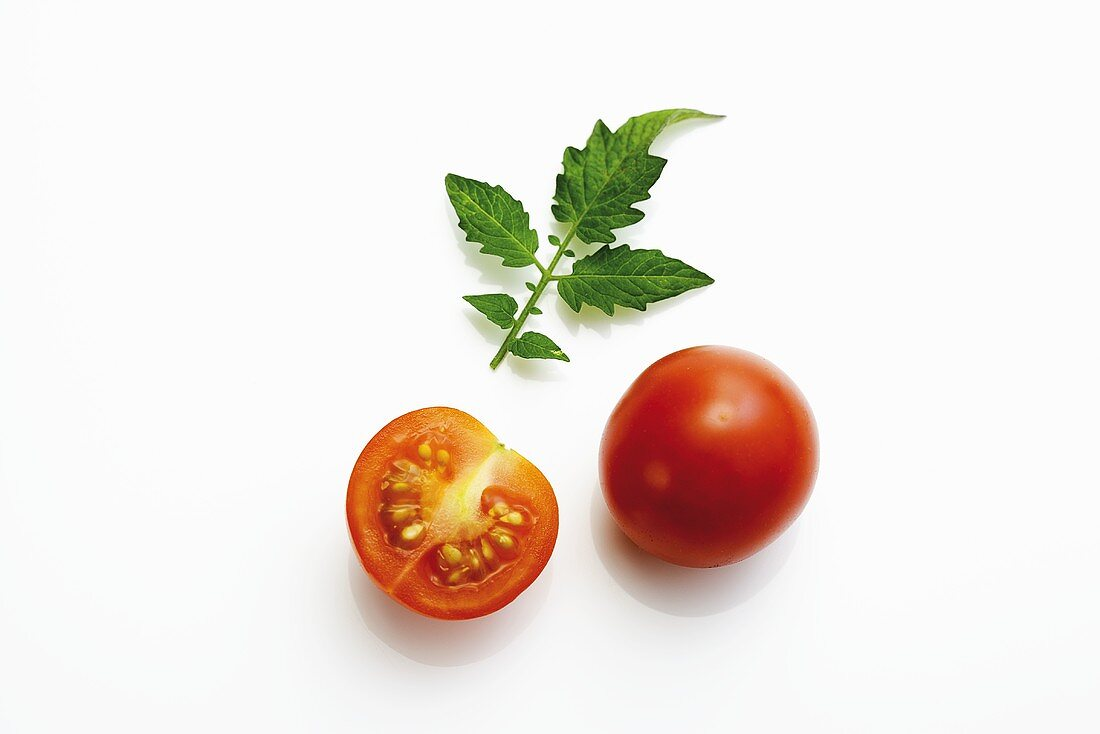 Whole and half cocktail tomato with tomato leaf