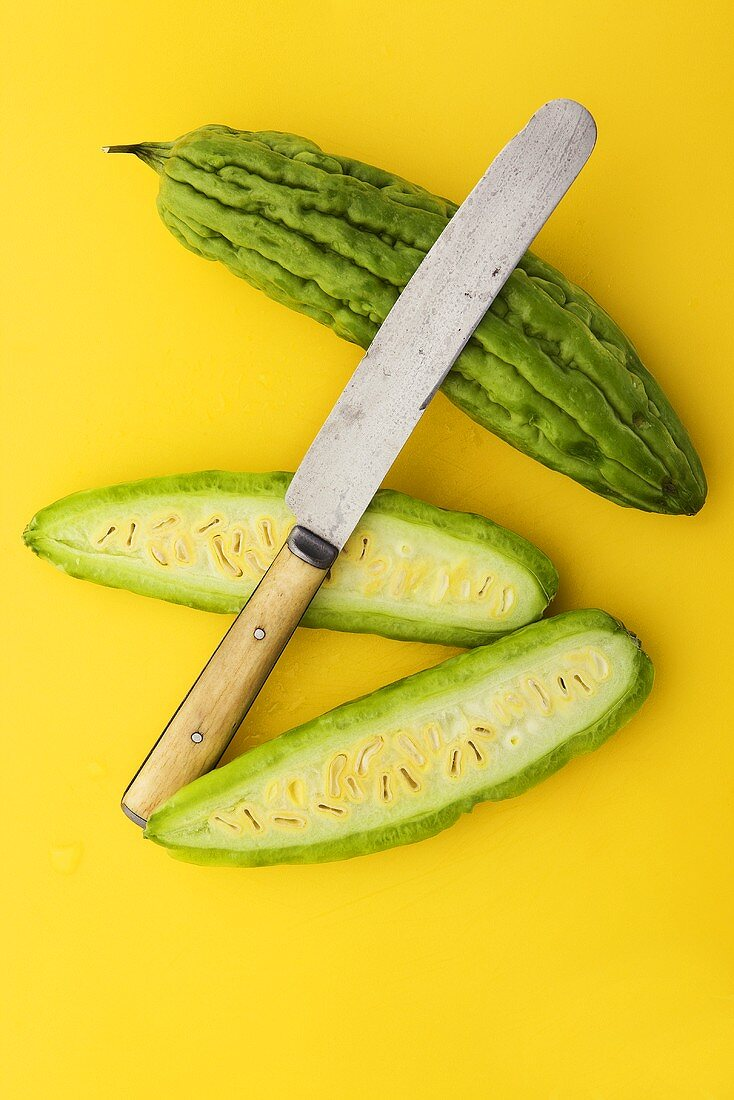 Whole and Halved Bitter Melon with Knife on Yellow Background